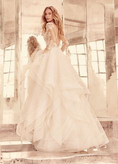 <p>Elysia</p>Ivory long sleeve lace bridal ball gown, V-front bateau illusion neckline, keyhole back with piping accent, cascading tulle skirt with thin double horsehair edging. Bridal Gowns, Wedding Dresses by Hayley Paige Bridal - JLM Couture - Bridal Style HP6556 by JLM Couture, Inc.