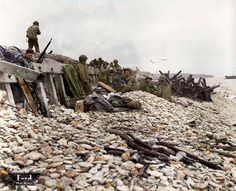 """Des marins américains se tiennent sur des galets devant un muret, probablement à Dog White, vers le 7 juin 1944. A Omaha, les 6 th et 7th U.S. Naval Beach Battalion (NBB) avec les 5th et 6th Engineer Special Brigade (ESB) sous les ordres du Brigadier General William M. Hoge formaient la Task Force 124.2 'Shore Party'.""  (Image Colourised by Dave Ford from Ohio, USA)"