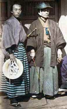 Two samurai, the one on the left is holding a jingasa, the one on the right is wearing a jingasa and holding a muchi (whip).