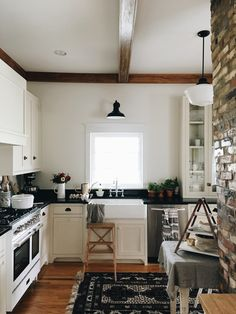 Linen kitchen cabinets, soapstone countertops, Schoolhouse sconce light over sink, Kohler sink and faucet, brick, beams