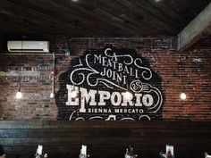 """The Emporio seal painted on the natural brick walls, """"ghost sign"""" style, by Ryan Hamrick"""