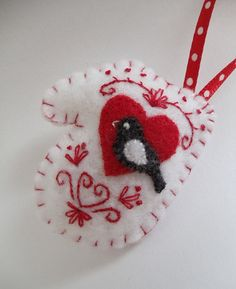 "Miniature Mitten Felt Ornament By myheartsdesire1871 @Etsy: $12.50. Mini mitten  features a tiny bird perched on a heart, surrounded by an original embroidery design. Lightly stuffed w/ fiberfill & finished w/ a loop of ribbon for hanging. Measures approx. 2""L X 1 3/4""W."