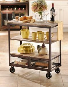 Wood and metal rolling cart for the kitchen. It has 3 shelves and 2 drawers for extra storage.