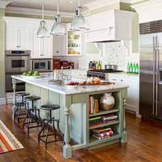 """But to mix it up, """"we gave the island four legs and a different color so it looks like furniture,"""" says John Varney, who made all the custom cabinetry. """"That treatment adds depth and vitality to a white kitchen."""" Deidra's pride lies in the kid-accessible features, however. """"Everything's just easy to get,"""" she says, """"and easy to put away."""" An island with hand-turned legs, painted cabinets with visible brushstrokes, and substantial trim give the s..."""