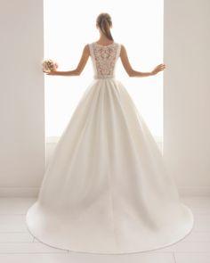 Fantástico vestido de novia clásico en raso con falda de gran volumen, escote barco y espalda escotada con insinuante dibujo hecho de una brillante pedrería. Perfecto vestido para la novia que busca la mezcla entre la sencillez, la sensualidad y la elegancia.