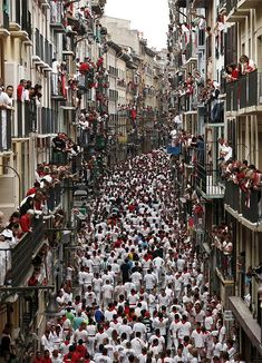 *PAMPLONA, SPAIN ~ The Running of the Bulls is part of a yrly festival in Pamplona, where bulls are let loose behind a crowd of people who try and outrun them on their course to the town's bull fighting ring. I couldn't help but be struck by this picture. It is exactly what I imagined the frenzied crowd + onlookers to look + feel like based on the description of the event in The Paris Wife!