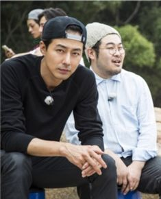 Jo In Sung can be seen looking in the direction of the camera, showing off his signature figure and alluring gaze. Despite being outdoors in simple clothes, he still looks like a model. Next to him, actor Kim Ki Bang is talking to someone else. The atmosphere of the set seems to be very comfortable and amiable. 1 night 2 days show