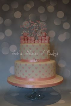 Heart studded wedding cake with baby blocks and heart spray