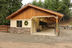 Open breezeway barn with board and batten gable ends, stone wainscot wrap and powder-coated stall fronts. This shedrow barn couldn't be any more perfect!