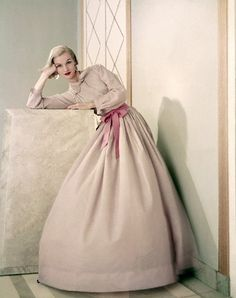 https://flic.kr/p/8BCPr9   May 1955   Model is wearing a pink dinner shirt tucked into light full skirt in sheer cotton chambray.  Image by Condé Nast Archive/Corbis