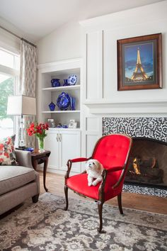 Black and white mosaic tile makes a big impact on the fireplace surround in this light and bright living room. Traditional moldings and built-in bookshelves give the fireplace wall even more distinction. A red chair pops in the mostly neutral space.