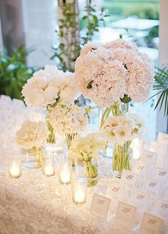 Elegant white escort cards are meticulously arranged around a centerpiece of all white tulips, hydrangeas, peonies and calla lilies.