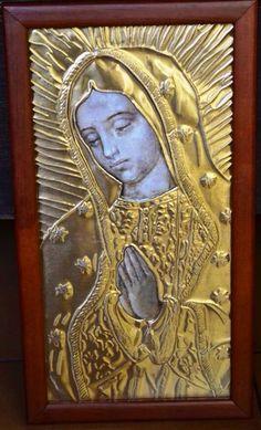 Cuadro Virgen de Guadalupe. Lo tenemos repujado en aluminio plateado, dorado y ocre.  Borde en madera caoba totalmente a mano con vidrio. Tamaño: 13 x 26 cm Bsf  25000