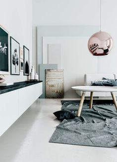 floating cabinetry + dark stone + rose gold pendant + white