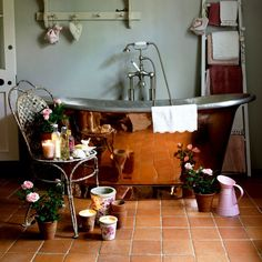bathroom with gray walls, copper tub, and terracotta floors (via house to home)