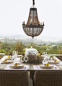 A wooden bead chandelier from Pottery Barn and weathered RH dining tables add rustic glam to the outdoor terrace. PHOTO: Laura Resen.