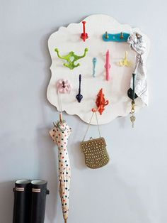 Use a precut wood plaque for the base (you can find them at any craft store) and screw in a mismatched jumble of painted hooks. Perfect right next to the door for keys, scarves, umbrellas and more.