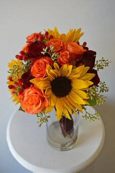 Fall bouquet with mini sunflowers, orange spray roses, black magic roses, red hypericum berries, and seeded eucalyptus.