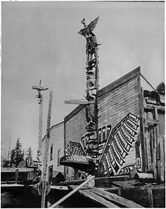 Alert Bay Totems - Totem pole - Totem poles in front of homes in Alert Bay, British Columbia in the 1900s.