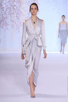 Fluid silver double satin robe with cut out shoulders, tulip draping and bow fastening.