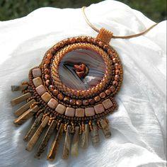 Damtien+Autorský+šperk.+Tento+šperk+je+vytvořen+časově+náročnou+technikou+korálkové+výšivky.+Krásný+donutek+polodrahokamu+achát+je+obšívaný+kvalitními+japonskými+korálky+TOHO,+doplněno+o+broušené+skleněné+korálky,+zlomky+polodrahokamu+jaspis+a+na+spodní+části+jsou+zavěšeny+korálky+z+obrázkového+jaspisu.+Přívěsek+je+podšit+umělou+semiší+alcantara+a...