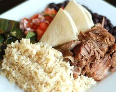 California Carnitas. Slow braised pork shoulder in Dr. Pepper, ginger and ancho chilies. Served with brown rice, black beans, and Salvadorian plantain tamale