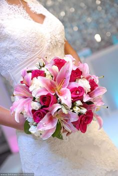 Soft romantic style pink orchids, hot pink roses, white flowers. Pretty wedding floral bouquet.