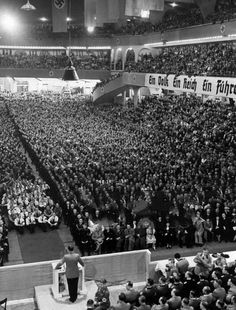 """With many thousands gathered at the Berlin Sportpalast, Adolf Hitler gives a fiery speech about the ongoing war in the West. He concludes with the statement: """"Our enemies, they already cry out today: Germany shall fall! But Germany can only give one answer: Germany will live and hence Germany will win!"""" Every attendee proceeds to give him an energetic standing ovation. January 30th, 1940."""