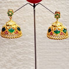 The jumkas are not fixed to the ear stud which gives you the flexibility to wear it with any earring. Pure brass, silver and enamel are heat treated and plated with 4-micron 23 carat gold for longevity. Stones used: Palakka and pink American cut stone.
