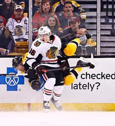 Teuvo Teravainen checks Johnny Boychuk in an amazing photo. The perfect placement of Boychuk's legs over the slogan behind him is hilarious!