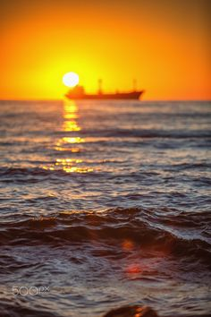 Cargo ship with containers in sunrise light - Sun setting at the sea with sailing cargo ship, scenic view