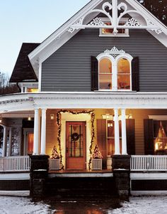 the front of a victorian style house with porch decorated for christmas