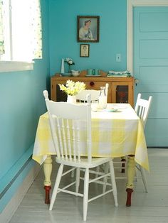 Color Breezes Into Cottage Style :: Despite its bright turquoise walls, this breakfast area reads unmistakably as cottage, thanks to the spindle-back chairs, gingham tablecloth, painted wood floors and old-fashioned sideboard.