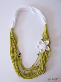 Handmade upcycled light green and white t-shirt necklace, with a removable flower brooch made from fabric, which you can use everywhere else you