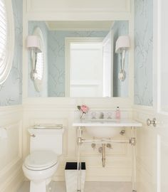 This elegant, transitional bathroom boasts gorgeous wainscoted walls with upper blue wallpaper embellished with silver branch patterns.