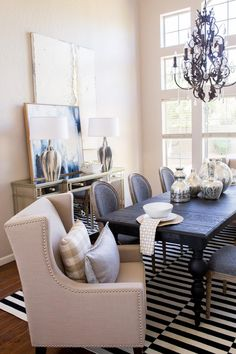 To add dimension to the living room design, a cushioned, nail head lined head chair rests at either end of this large dining table.