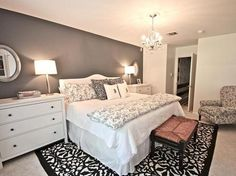 budget bedroom decor ideas Why this one? Matching lamps, Focus wall, White bed with perfect amount of pillows, Comfortable chair, White side tables with lots of storage, & Area carpet under the bed.