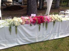 An ombre of flowers flows down the head table. #bandbdesigns #renotahoeweddings www.bandbflowerdesigns.com