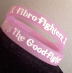 """Here they are! The 2013 FFZ wristbands! These 0.5 inch ink injected wristbands are lavender in color and feature the message: """"Fibro Fighterz"""" on one side, and on the other """"Fight The Good Fight!"""", and on the inside they are inscribed with the gentle reminder of """"never give up""""."""
