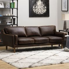 This soft sofa is composed of luxurious Columbus leather upholstery in a chocolate color with polyurethane foam, duck feathers and polyester fiber couched within. The sturdy wood legs are are finished in a lovely and bold oak finish.