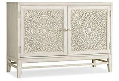 This two-door chest has intricate carvings that are highlighted by a warm white finish. The doors open to reveal an adjustable shelf for versatile storage.