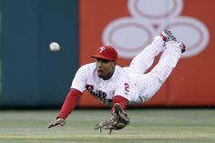 Philadelphia Phillies center fielder Ben Revere dives for a fly out by St. Louis Cardinals' Carlos Beltran during the first inning of a base...