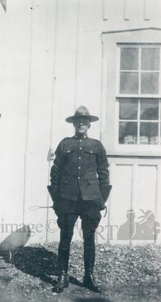 FMP.80.337.6    circa 1920    Photograph of a Mountie standing outside a wooden building with a riding crop in hand.