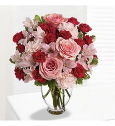 Floral bouquet/arrangement with pink roses, red spray roses, pink alstroemeria and pink carnations accented with assorted greenery in a glass vase.