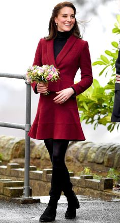 Kate Middleton in a red coat dress over a black turtleneck, tights and boots
