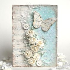 handmad shabby chic card ... soft colors: creamy white, gray, aqua ... white washed .. butterfly of book paper ... artfully arranged dimensional flowers and buttons ...