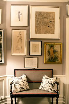 Beautifully arranged prints and paintings in a hallway make such a fabulous statement. Love the settee with the pillows too.