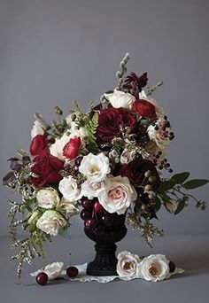 Other tables will have gold compote vases filled with cream hydrangeas, beige roses, deep red spray roses, burgundy scabiosa flowers, gold seeded eucalyptus, white wax flowers, white tulips, and brown scabiosa pods surrounded by gold mercury glass votives.