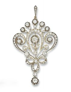 A RUSSIAN ANTIQUE DIAMOND PENDANT/BROOCH   The cartouche-shaped floral old-cut diamond panel suspending a diamond two-stone drop, mounted in silver and gold, with brooch fitting, circa 1905, 7.5 cm long, with 56 zolotnik mark, in fitted celluloid case