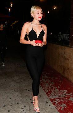 Miley Cyrus usa em street style look um macacão preto longo com salto